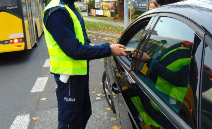 KPP Oświęcim. Policjant dokonuje badania trzeźwości kierowcy